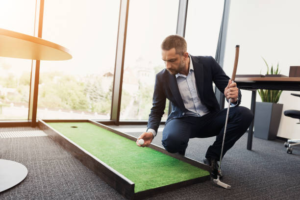 A man in a business suit plays mini golf. He is in a modern modern office